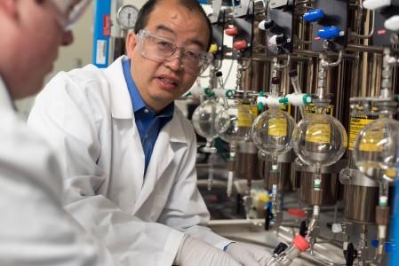 Hongcai (Joe) Zhou instructs a student in the research laboratory.